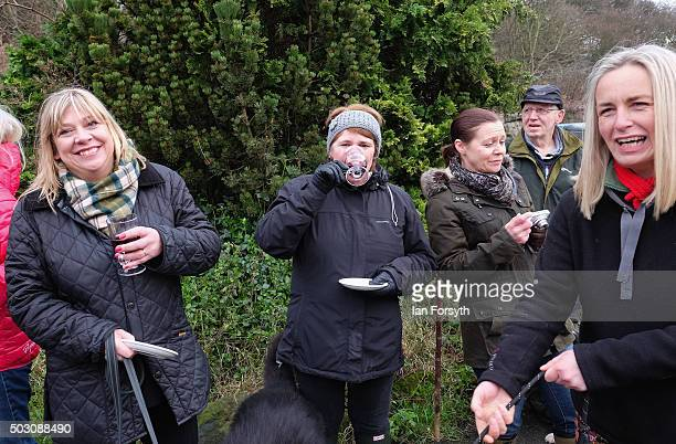 Spectators enjoy a drink as horses, riders and hounds from the Cleveland Hunt prepare to ride out on the traditional New Year's Day hunt on January...