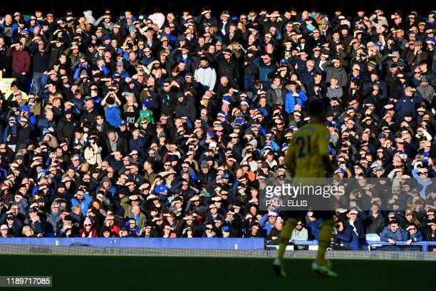 Spectators enjoy the sunshine during the English Premier League football match between Everton and Arsenal at Goodison Park in Liverpool north west...