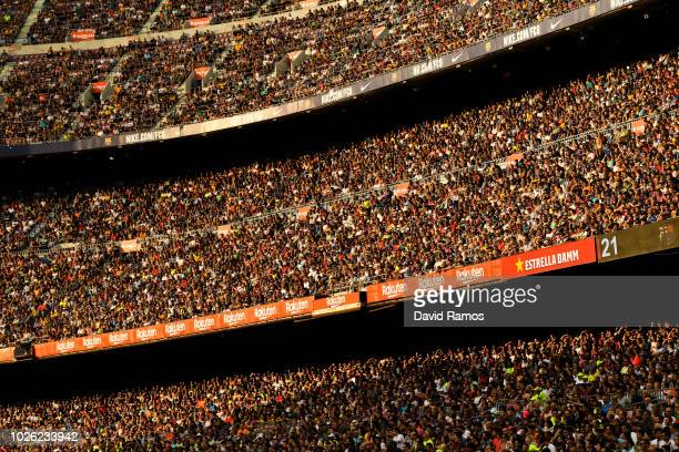 Spectators follow the action from the stands during the La Liga match between FC Barcelona and SD Huesca at Camp Nou on September 2, 2018 in...