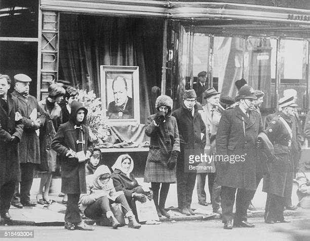 Spectators gather along a London street to watch the funeral procession for Sir Winston Churchill whose portrait is displayed behind them in a shop...