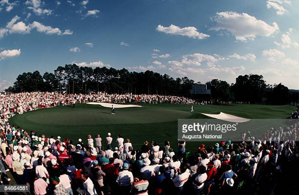 Spectators gather around the 18th green as Jack Nicklaus and Greg Norman approach during the 1990 Masters Tournament at Augusta National Golf Club on...