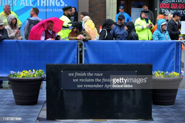 Spectators gather around the unfinished memorial to the Boston Marathon bombings located near where Krystle Campbell died in 2013 on Boylston Street...