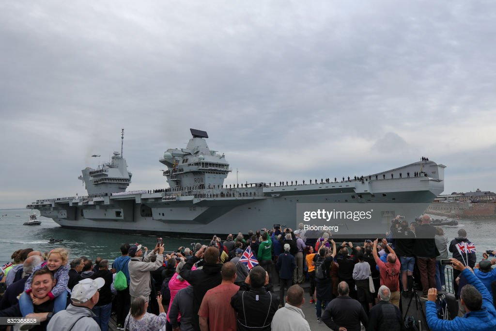Spectators gather as the U.K.'s Royal Navy new aircraft carrier, HMS Queen Elizabeth arrives at its home port in Portsmouth, U.K., on Wednesday, Aug. 16, 2017. The largely French-designed ship will carry 40 aircraft and about 700 crew members was built by a joint venture between BAE Systems Plc, Babcock International Group Plc and Thales SA. Photographer: Luke MacGregor/Bloomberg via Getty Images