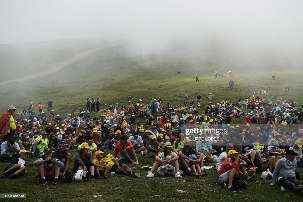 TOPSHOT - Spectators gather on a foggy mountain slope to watch the arrival of the 17th stage of the 105th edition of the Tour de France cycling race, between Bagneres-de-Luchon and Saint-Lary-Soulan Col du Portet, southwestern France, on July 25, 2018.