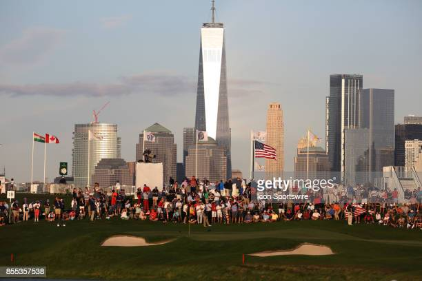 Spectators gather on the 18th hole with the New York skyline in the background during the first round of the Presidents Cup on September 28 at...
