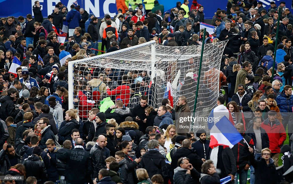 Spectators gather on the pitch after news of the bombing and terrorist attacks in Paris reaches the fans after the International Friendly match between France and Germany at the Stade de France on November 13, 2015 in Paris, France.