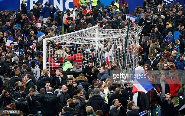 Spectators gather on the pitch after news of the bombing and terrorist attacks in Paris reaches the fans after the International Friendly match...