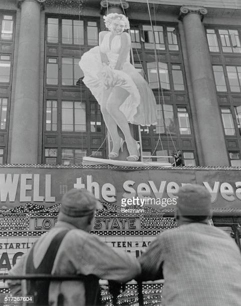 Spectators gawk in Times Square as a fiftytwofoot figure of Marilyn Monroe is erected on the front of Loew's State Theatre The fourandahalfstory...