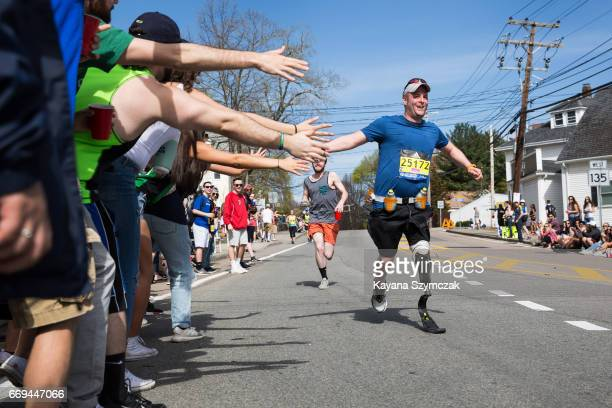 Spectators give high fives to a disabled runner as he makes his way past the 6 mile mark of the Boston Marathon on April 17 2017 in Framingham...