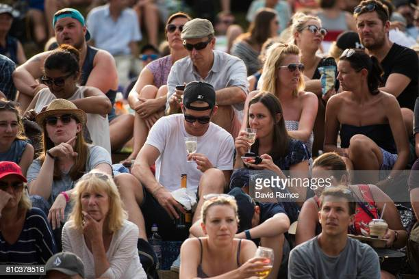 Spectators have Champagne strawberries and cream on 'Murray Mound' on day five of the Wimbledon Lawn Tennis Championships at the All England Lawn...