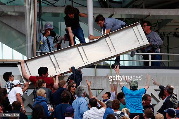 Spectators help lift a piece of the roof from Court Philippe Chatrier that blew off in high winds during the Men's quarter final match against...