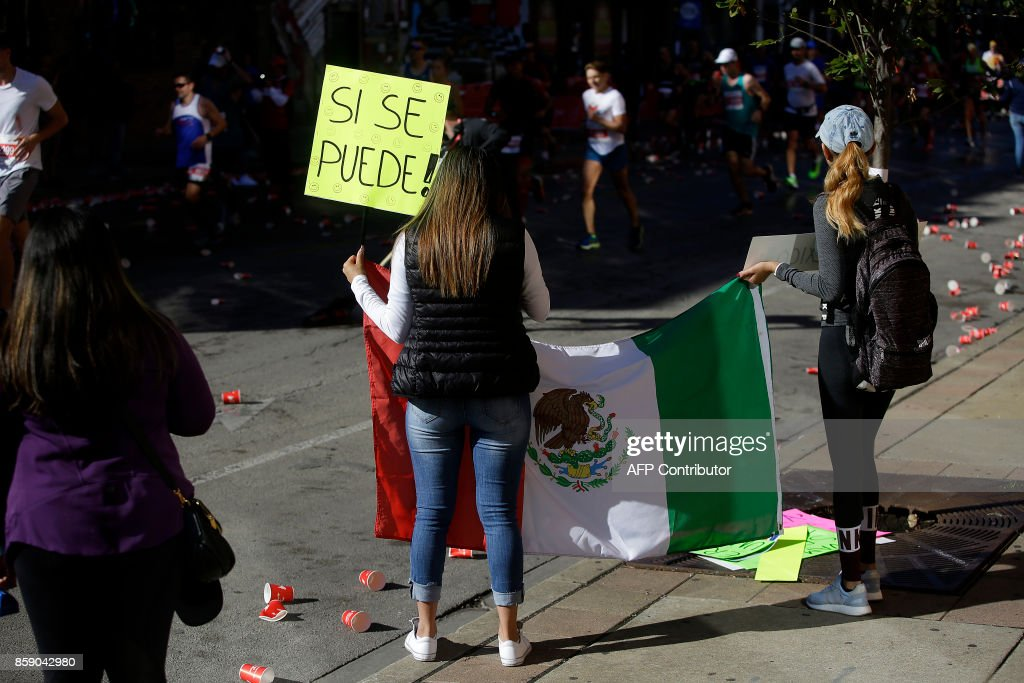 Spectators hold a Mexican flag as participants run by during the Chicago Marathon on October 8, 2017 in Chicago, Illinois. / AFP PHOTO / Joshua Lott