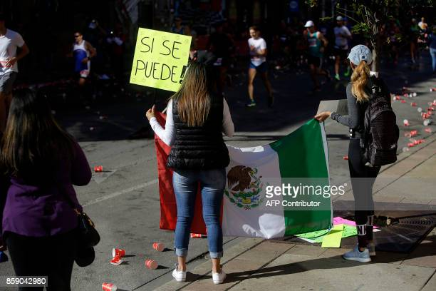 Spectators hold a Mexican flag as participants run by during the Chicago Marathon on October 8 2017 in Chicago Illinois / AFP PHOTO / Joshua Lott