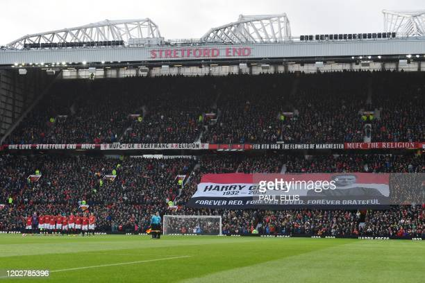 Spectators hold aloft a banner in honour of the late Manchester United goalkeeper and Munich Air Disaster hero Harry Gregg as the teams observe a...