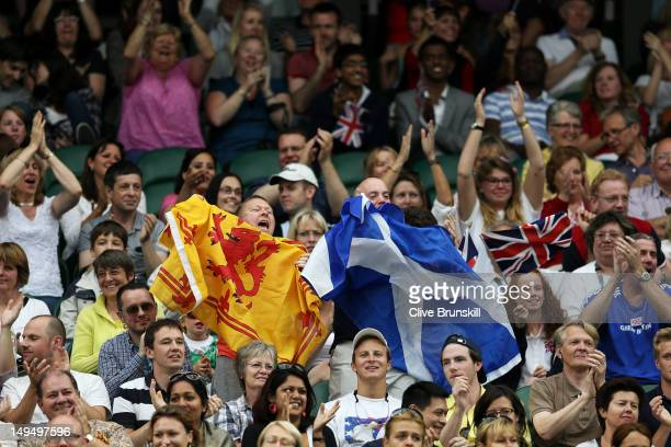 Spectators hold flags during the Men's Singles Tennis match between Andy Murray of Great Britain and Stanislas Wawrinka of Switzerland on Day 2 of...