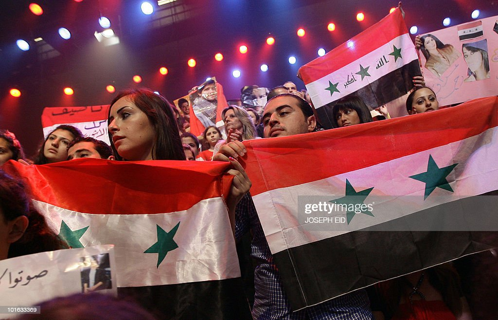 Spectators hold Syrian flags as they attend the Star Academy final show, a highly successful pan-Arab television show produced by Lebanese Broadcasting Corporation International (LBCI), at its studios in Adma, north of Beirut, late on June 4, 2010.