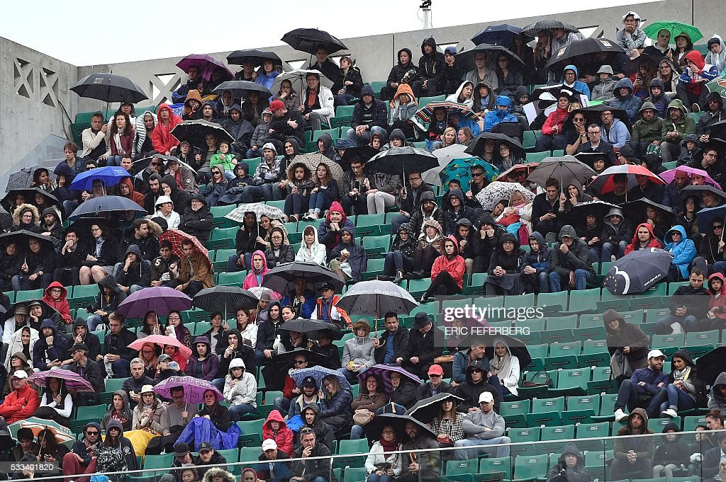 TOPSHOT - Spectators hold umbrellas as they watch Japan's Kei Nishikori and Italy's Simone Bolelli during their men's first round match at the Roland Garros 2016 French Tennis Open in Paris on May 22, 2016. / AFP / Eric FEFERBERG