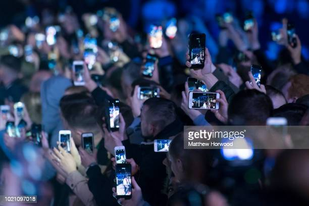 Spectators hold up mobile phones at an event on May 2, 2018 in Cardiff, United Kingdom.