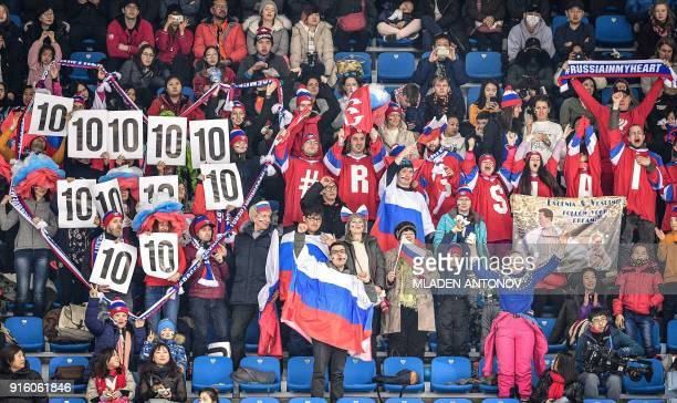 Spectators hold up placards in support of Russia's Mikhail Kolyada during the figure skating team event men's single skating short program during the...