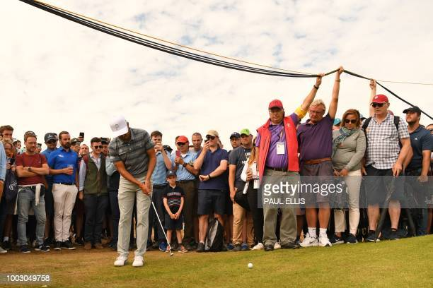 Spectators hold up television cables so that US golfer Rickie Fowler can play onto the 6th green during his third round on day 3 of The 147th Open...