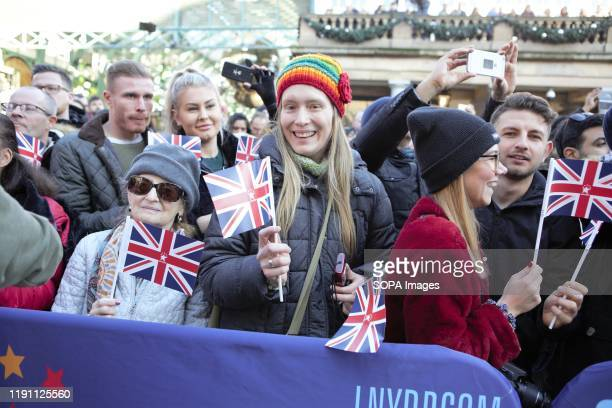 Spectators holding UK Flags during London's New Year's Day Parade 2020 Preview Show at Covent Garden Piazza.