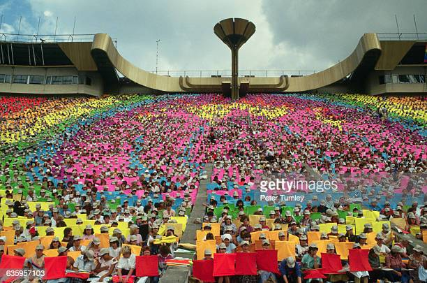 Spectators in a stadium hold colorful banners during the opening ceremonies of the 1986 Goodwill Games