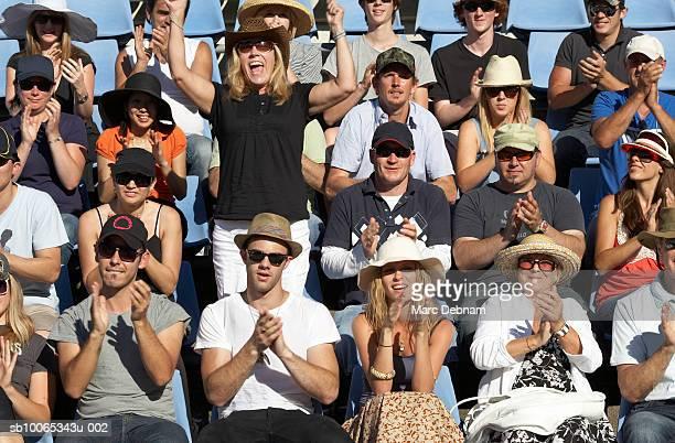 Spectators in crowd applauding