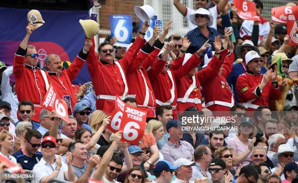 Spectators in fancy dress cheer during the 2019 Cricket World Cup group stage match between England and South Africa at The Oval in London on May 30,...