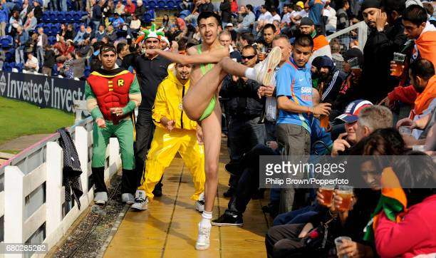 Spectators in fancy dress including one wearing a mankini kick a tennis ball around before the fifth oneday international cricket match between...