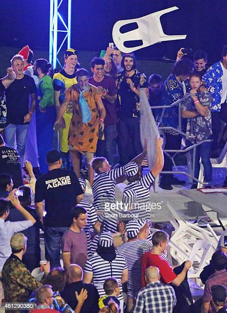 Spectators in fancy dress throw chairs and tables during the final between Simon The Wizard Whitlock and Mighty Michael van Gerwen during the...