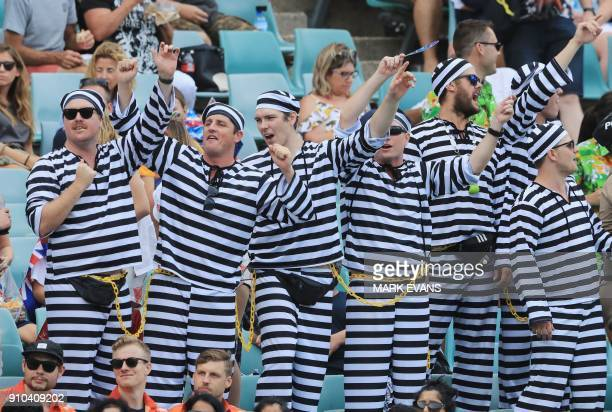 Spectators in prisoner style fancy dress react on the stands during the Sydney World Rugby Sevens Series tournament in Sydney on January 26 2018 /...