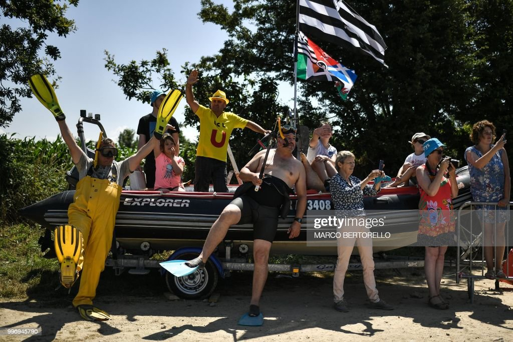 Spectators in scuba diving outfits stand by the route to cheer riders during the sixth stage of the 105th edition of the Tour de France cycling race between Brest and Mur-de-Bretagne Guerledan, western France, on July 12, 2018.