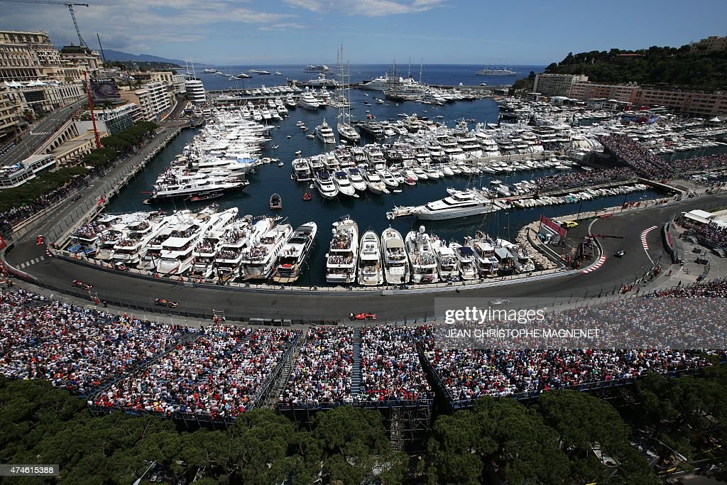 Spectators in terraces watch drivers racing along Monaco's harbour at the Monaco street circuit in Monte-Carlo on May 24, 2015, during the Monaco Formula One Grand Prix.