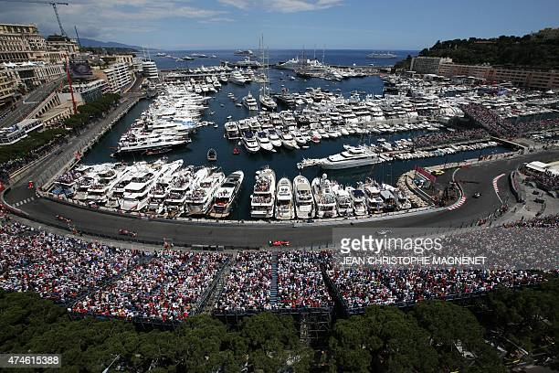 Spectators in terraces watch drivers racing along Monaco's harbour at the Monaco street circuit in Monte-Carlo on May 24 during the Monaco Formula...