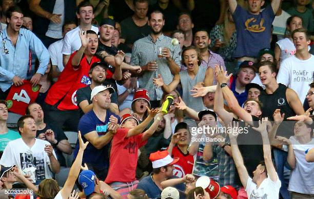 Spectators in the crowd attempt to catch a six hit by Dwayne Bravo of the Renegades during the Big Bash League match between the Melbourne Renegades...