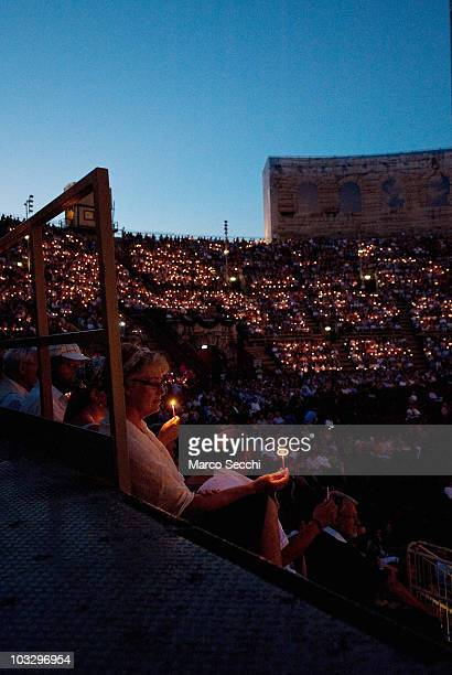 Spectators in the gallery follow the tradition of lighting candles at the start of the performance of 'Aida' on August 8 2010 in Verona Italy The...
