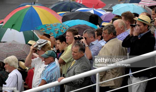 Spectators in the rain watch The Lillie Langtry Fillies' Stakes at Goodwood Racecourse