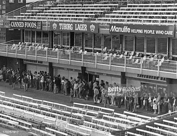 Spectators in the stands sheltering from the rain during a County Championship match between Middlesex and Lancashire at Lord's Cricket Ground London...