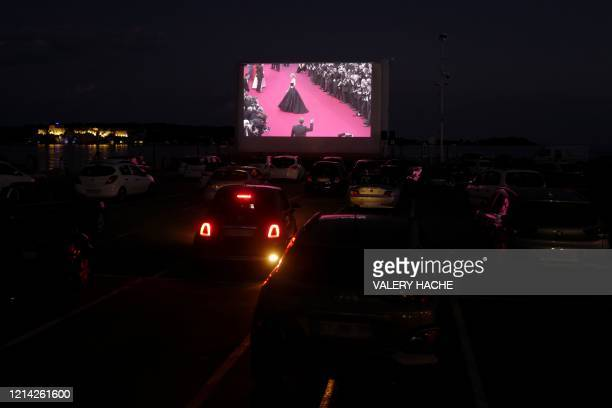 Spectators in their vehicle attend a drivein movie screening in the French riviera city of Cannes southern France on May 20 as part of Cannes...