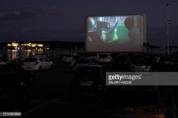 Spectators in their vehicle attend a drivein movie screening of ET by US director Steven Spielberg in the French riviera city of Cannes southern...