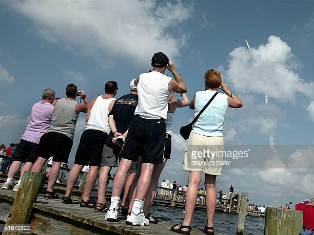 Spectators in Titusville, Florida, watch the space shuttle Atlantis lifts off off from launch pad 39-B at the Kennedy Space Center 07 October, 2002....