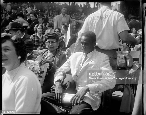 Spectators including Luisa Clemente mother of Roberto Clemente and brother Justino Clemente in stands at 1960 World Series opening baseball game with...