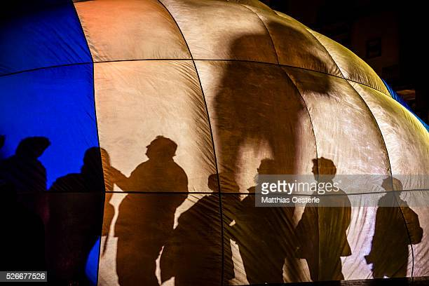 Spectators inside a recycled hot air balloon cast shadows as they take part in the 'Iglu de vent' performance during the city's light festival 'Llum...