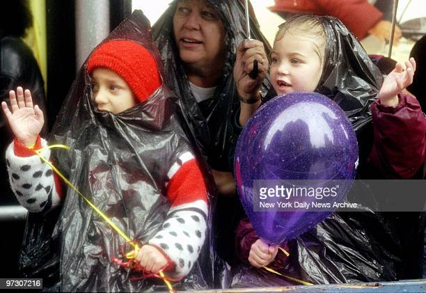Spectators inTimes Square cover up against the pouring rain during the 72nd annual Thanksgiving Day Parade
