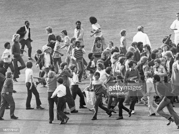Spectators invade the pitch after West Indies batsman Clive Lloyd made a century on the first day of the 1st Test against England at the Oval cricket...