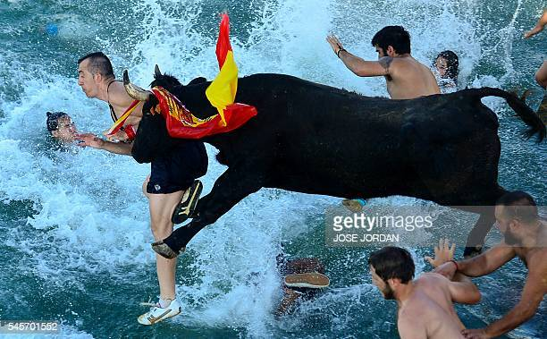 TOPSHOT Spectators jump into the port followed by a bull during the traditional running of bulls 'Bous a la mar' on Denia's harbour near Alicante on...