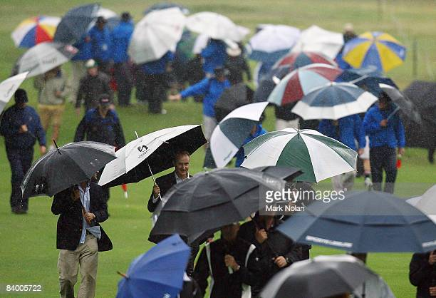 Spectators leave the course after bad weather halted play during the second round of the 2008 Australian Open at The Royal Sydney Golf Club on...