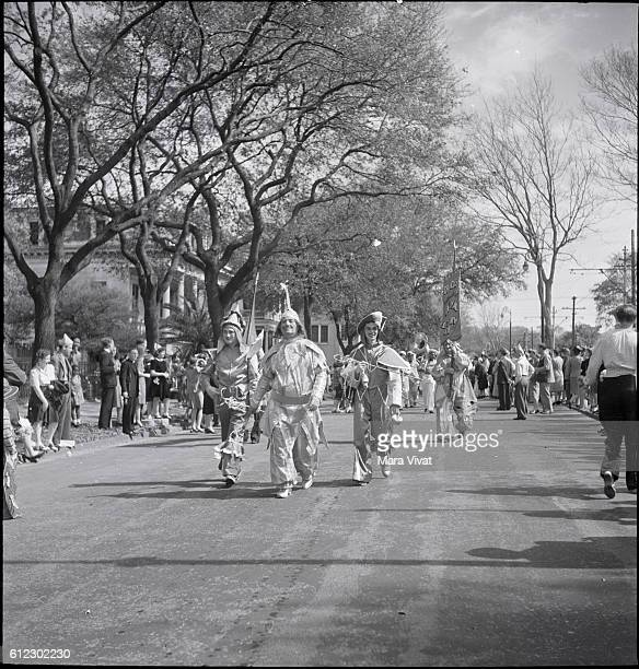 Spectators line a street to watch a Mardi Gras club hold their costume parade in New Orleans Louisiana circa 1950