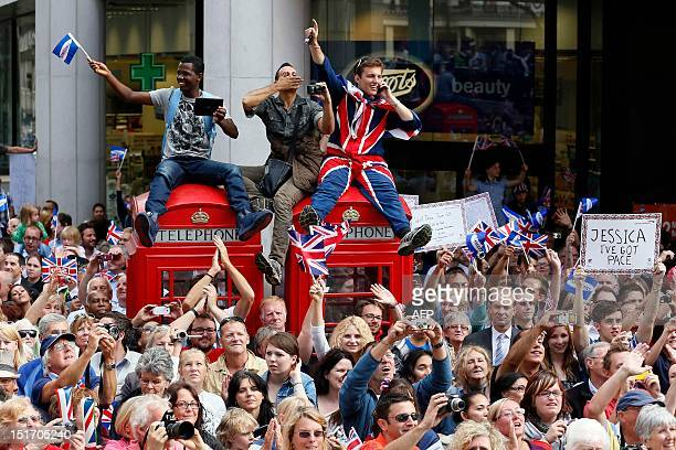 Spectators line streets to watch a parade celebrating Britain's athletes who competed in the London 2012 Olympic and Paralympic Games in central...