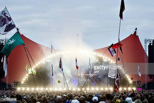Spectators listen and wave flags as British band The Cure performs on July 5 2012 at the Roskilde Festival in Roskilde AFP PHOTO / SCANPIX / TORKIL...
